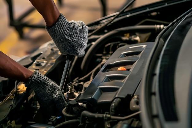 De cerca, la gente está reparando un automóvil. use una llave y un destornillador para trabajar en el garaje.