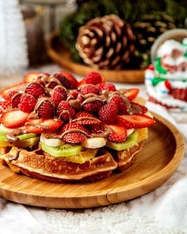 Cerca de gofres con frutas adornadas con chocolate