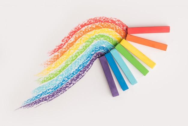 Cerca del gradiente de arco iris hecho de tizas de crayón pastel sobre las huellas coloridas