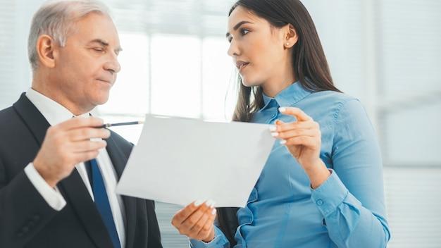 De cerca. grupo de empleados discute el informe financiero anual. trabajando con documentos
