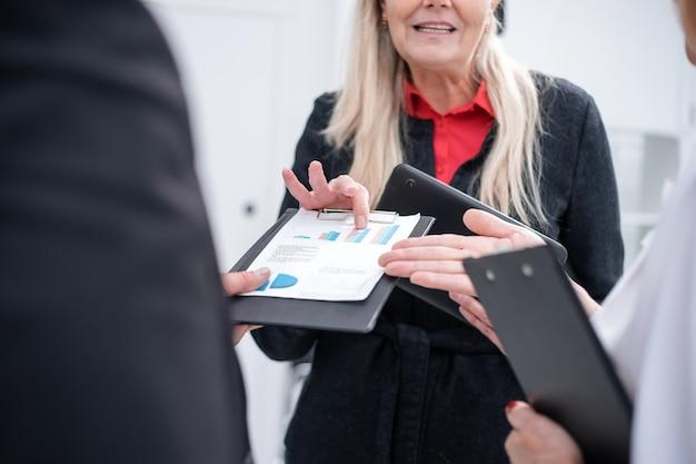 De cerca. grupo de empleados discutiendo horarios financieros. concepto de negocio
