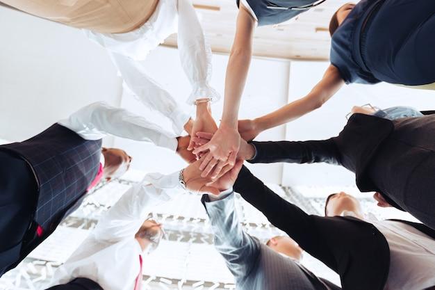 Cerca del grupo de empresarios poniendo sus manos una encima de la otra