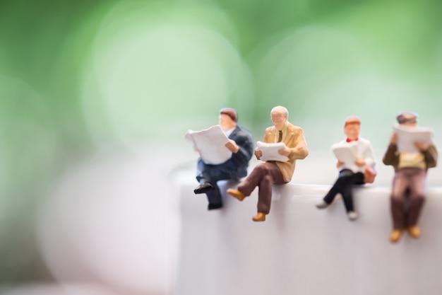 Cerca de un grupo de mini figuras en miniatura, el hombre y la mujer se sientan y leen un libro y un periódico en una taza