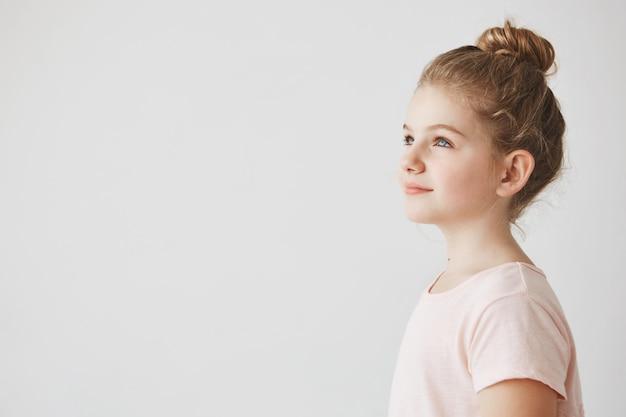 Cerca de la guapa niña con cabello rubio en peinado de moño, de pie en tres cuartos, mirando a un lado con una sonrisa en su rostro.