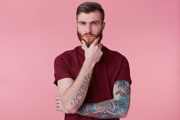 Cerca de guapo chico barbudo pensativo con mano tatuada, mirando a cámara, sosteniendo su barbilla, piensa en su futuro, hacer planes, sueños, aislado sobre fondo rosa.