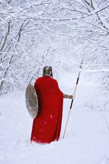 Cerca de guerrero espartano caminando por el bosque de invierno