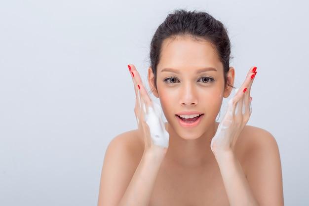 Cerca de la hermosa cara asiática en forma de v con espuma limpiadora para el cuidado de la piel
