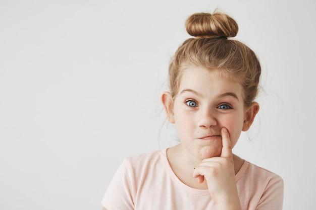 Cerca de la hermosa chica con cabello rubio en peinado de bollo sosteniendo el dedo cerca de la boca, haciendo expresión de la cara divertida, divirtiéndose en sesión de fotos.