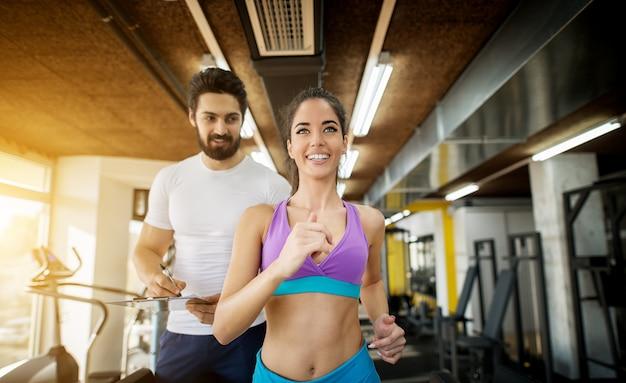 Cerca de la hermosa joven atractiva feliz satisfecha fitness chica practicando en la caminadora en el soleado gimnasio moderno con un guapo entrenador personal barbudo de pie detrás de ella con un portapapeles.
