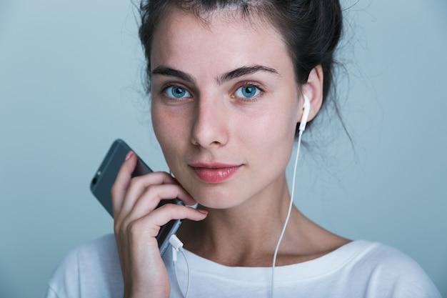 Cerca de una hermosa joven casual que se encuentran aisladas sobre fondo azul, escuchando música con auriculares y teléfono móvil