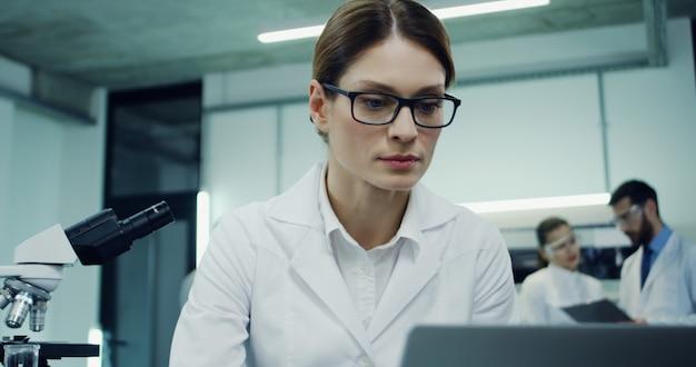 Cerca de la hermosa joven caucásica en gafas trabajando en el laboratorio y mirando en el microscopio, luego escribiendo en la computadora portátil. cámara alejándose.