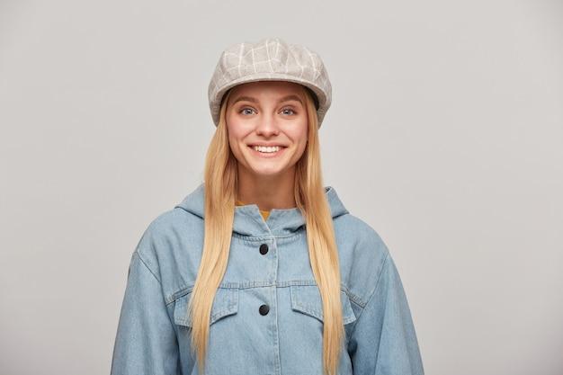 Cerca de una hermosa joven rubia con el pelo largo hacia abajo, mirando feliz sonriendo