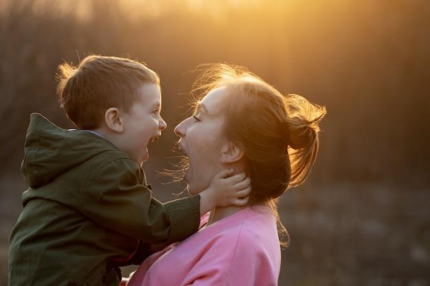Cerca de una hermosa madre y su hijo divirtiéndose al aire libre. niño lindo sujeto por su madre en los brazos que se ríe contra la puesta de sol. concepto del día de la madre