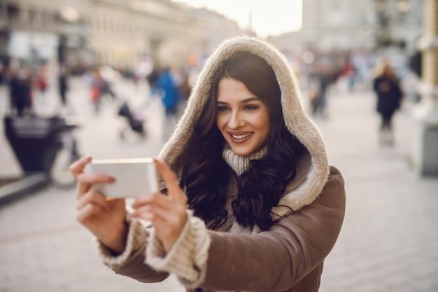 Cerca de hermosa mujer caucásica con cabello largo castaño de pie en la calle en clima frío en abrigo y tomando autorretrato.