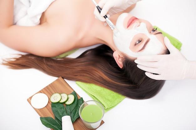 Cerca de hermosa mujer joven acostada con los ojos cerrados y cosmetóloga aplicando máscara facial con pincel en spa