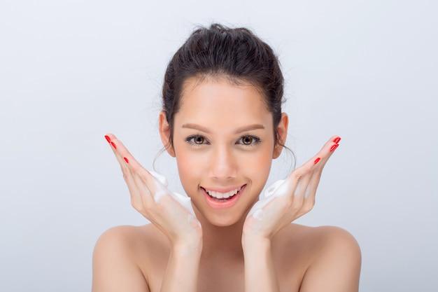 Cerca de hermosa mujer joven con espuma limpiadora para el cuidado de la piel