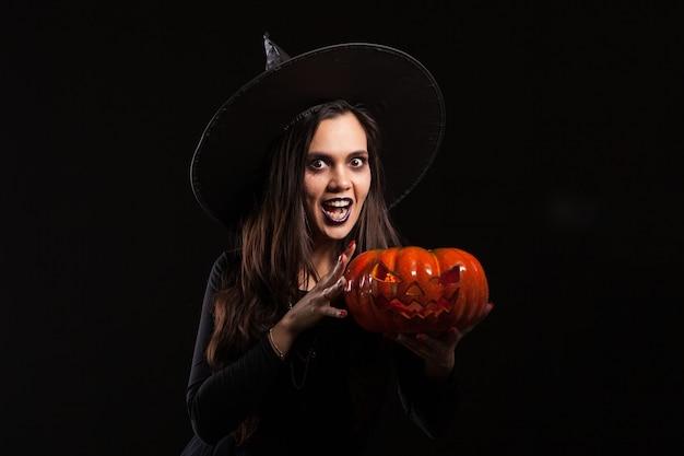 Cerca de hermosa mujer morena en ropa de estilo halloween con calabaza en las manos y mirando a la cámara sobre fondo negro. calabaza aterradora.