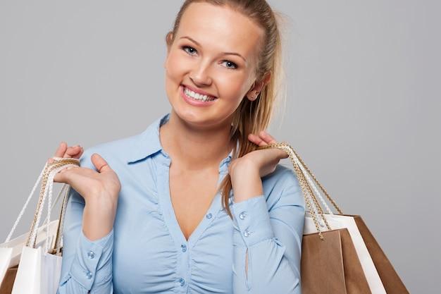 Cerca de hermosa mujer rubia llena de bolsas de la compra.