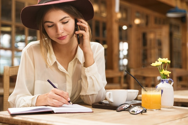 Cerca de una hermosa mujer con sombrero sentado en la mesa de café