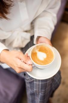 Cerca de hermosa mujer está tomando café