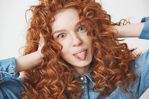 Cerca de hermosa niña de jengibre tocando el cabello sonriendo mostrando la lengua