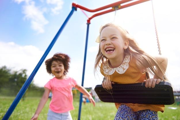 Cerca de hermosas chicas jóvenes jugando con columpio