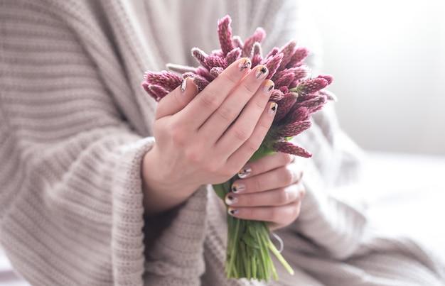 Cerca de hermosas manos femeninas con gran taza blanca de café capuchino y flores.