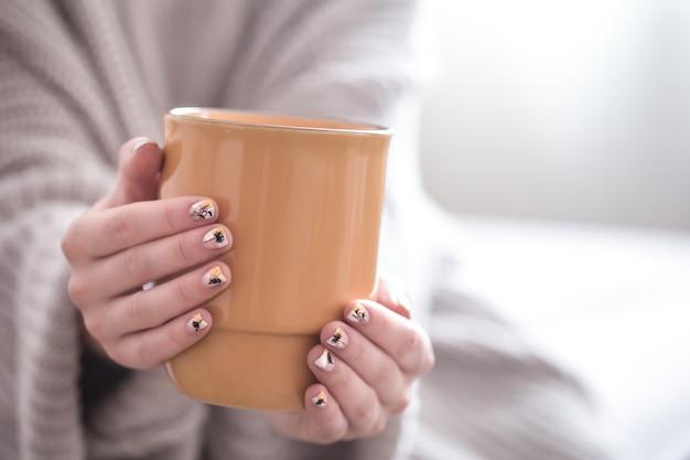 Cerca de hermosas manos femeninas sosteniendo una gran taza blanca de flores y café capuchino