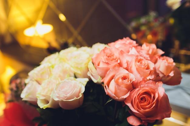 Cerca de un hermoso ramo de rosas en colores suaves. fondo de bockeh, restaurante en sordos. poca profundidad de foco. flor de concepto para ti.