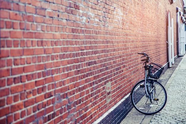 Cerca de un hermoso soporte de bicicleta negro solo cerca de la pared de ladrillo rojo al aire libre.