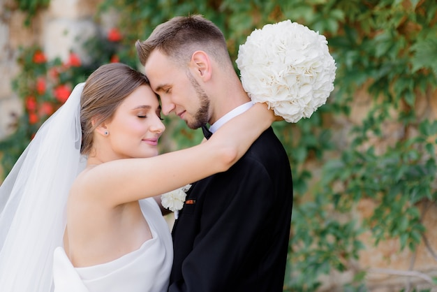 Cerca de hermosos recién casados abrazándose en la calle