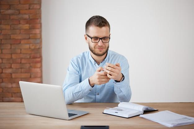 Cerca del hombre sin afeitar maduro con gafas y camisa en el trabajo, charlando con la esposa por teléfono inteligente durante el almuerzo.