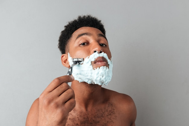Cerca de un hombre africano desnudo concentrado afeitado