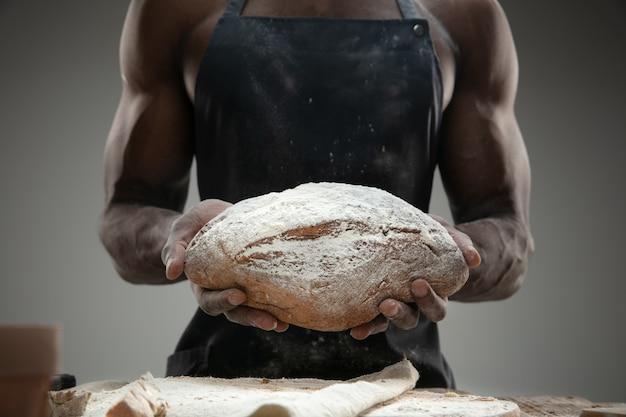 Cerca de hombre afroamericano cocina cereales frescos, pan, salvado en la mesa de madera. comida sabrosa, nutrición, producto artesanal. alimentos sin gluten, estilo de vida saludable, fabricación ecológica y segura. hecho a mano.