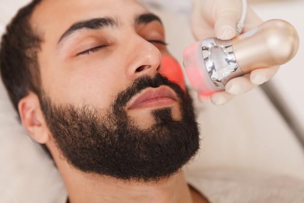 Cerca de un hombre barbudo obteniendo un procedimiento de elevación de rf rejuvenecedor por cosmetólogo