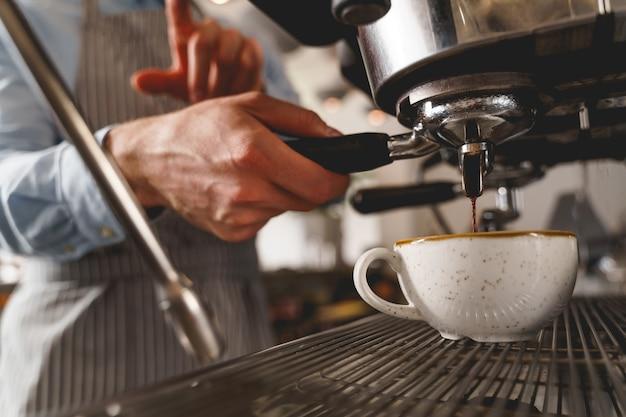 Cerca del hombre bartender mano sujetando la manija de la máquina de café y vertiendo bebida caliente en una taza blanca del grifo