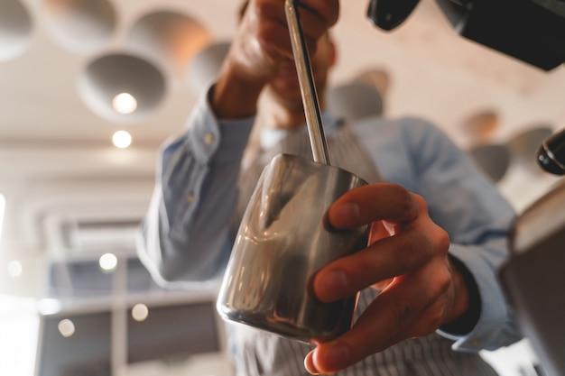 Cerca de hombre bartender manos sosteniendo taza metálica y vertiendo bebida caliente del grifo de la máquina de café