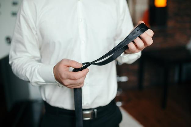 Cerca del hombre en camisa vestirse y ajustar la corbata en el cuello en casa.
