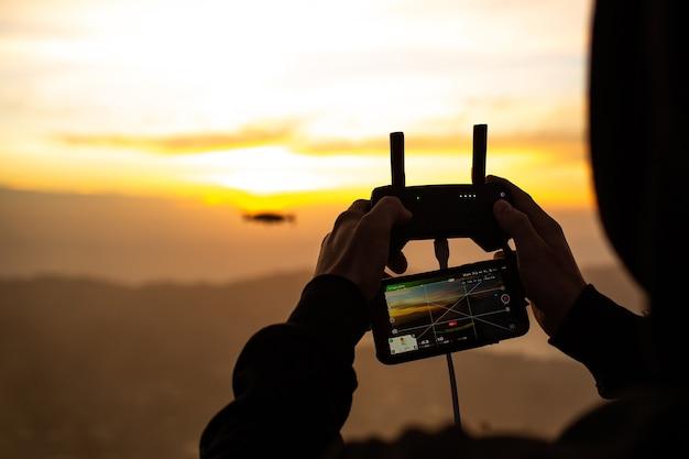 De cerca. un hombre controla un dron bajo el sol del amanecer en el volcán batur. bali, indonesia