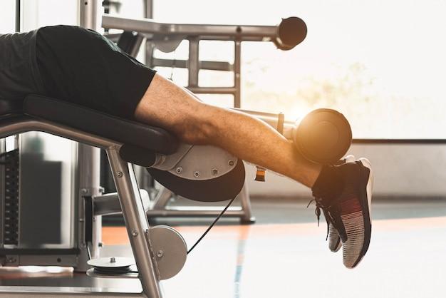 Cerca del hombre de deporte que estira y levanta peso con las dos piernas cuando está boca abajo para estirar