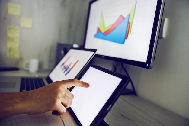 Cerca del hombre desplazándose en la tableta y trabajando en el análisis del salario mensual. en las pantallas hay gráficos. interior de la oficina en casa.