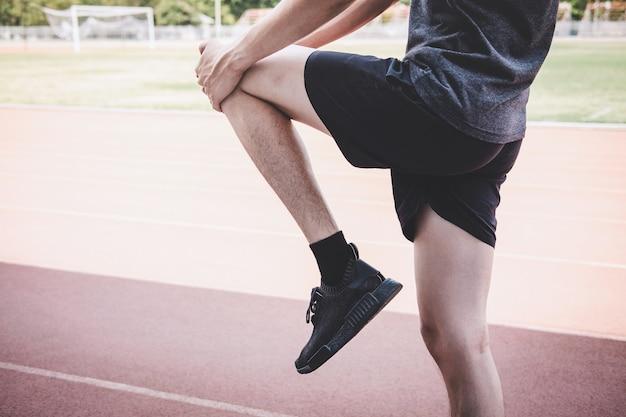 Cerca de un hombre estirando su pierna