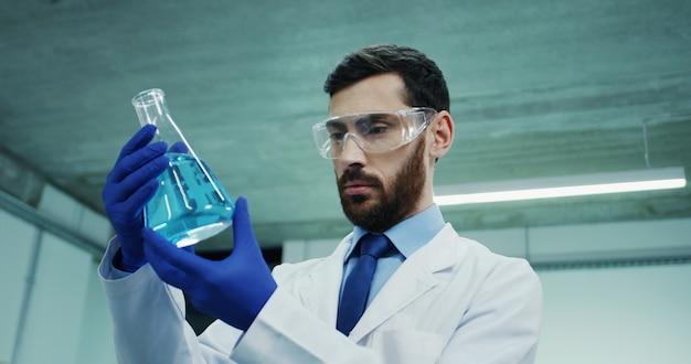 Cerca del hombre guapo del cáucaso, científico de laboratorio en las gafas y túnica blanca, mirando el tubo de ensayo con líquido azul mientras realiza el análisis.