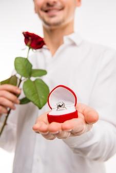 Cerca de un hombre guapo con una rosa roja y un anillo de bodas