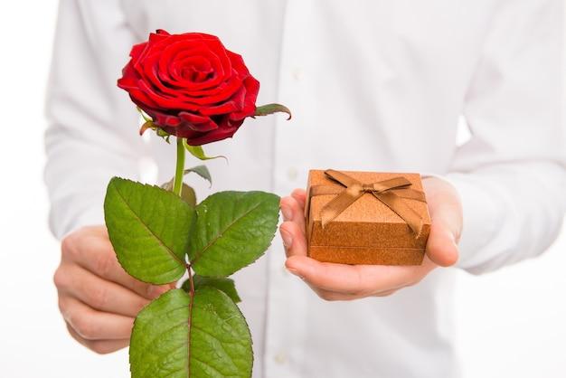 Cerca de un hombre guapo con una rosa roja y presente