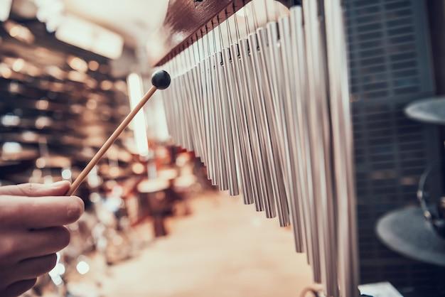 De cerca. el hombre está jugando bar carillones en la tienda de música.