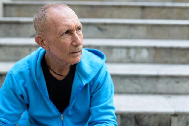 Cerca del hombre mayor calvo pensando mientras está sentado en la escalera