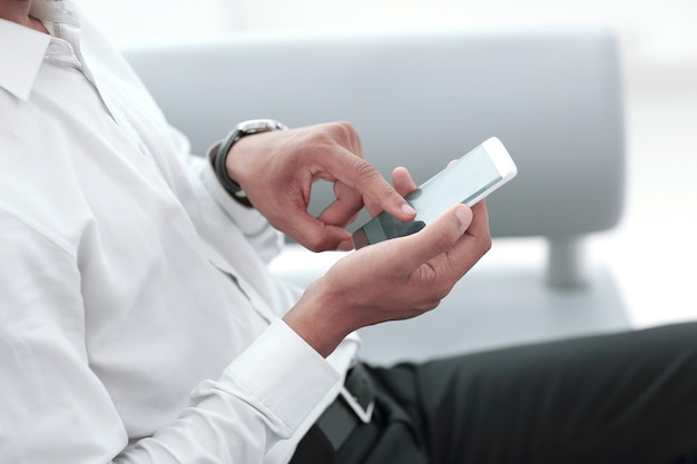 De cerca. hombre moderno escribiendo en su teléfono inteligente. personas y tecnologia