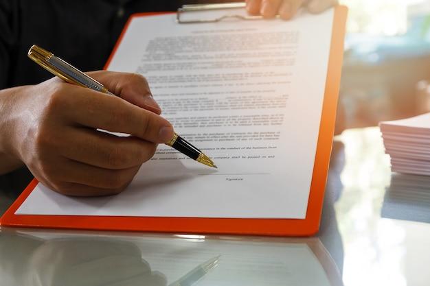 Cerca del hombre de negocios que firma el contrato que hace un trato