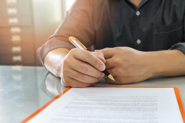 Cerca del hombre de negocios que firma el contrato que hace un trato.
